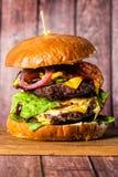 Двойной бургер на доске на деревянной предпосылке Стоковое Фото