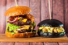 Двойной бургер на доске на деревянной предпосылке Стоковые Фото