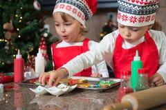 Двойные девушки в красном цвете делая печенья рождества Стоковое Фото