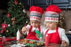 Двойные девушки в красном цвете делая печенья рождества Стоковые Фотографии RF