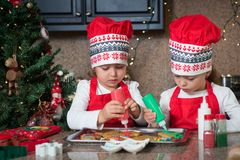 Двойные девушки в красном цвете делая печенья рождества Стоковые Изображения RF