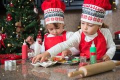 Двойные девушки в красном цвете делая печенья рождества Стоковое Изображение RF