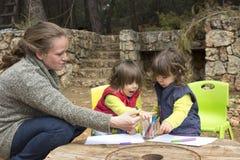 Двойные девушки малыша рисуя на бумажное внешнем Стоковая Фотография RF
