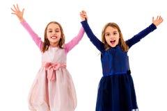 Двойные девушки празднуют при поднятые руки держащ руки Стоковые Изображения RF