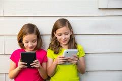 Двойные девушки сестры играя с ПК таблетки счастливым на белой стене Стоковое Изображение