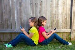Двойные девушки сестры играя smartphone сидя на лужайке задворк Стоковое фото RF