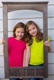 Двойные девушки сестры представляя с постаретой деревянной рамкой границы Стоковые Фото