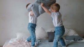Двойные малыши мальчиков лежат на кровати, бросая подушках, скакать и смеяться над видеоматериал