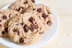 Двойные печенья обломока шоколада на белой плите в расслабляющем времени Стоковое фото RF