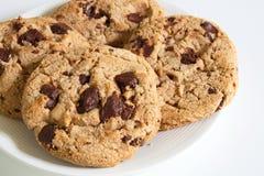 Двойные печенья обломока шоколада на белой плите в расслабляющем времени Стоковая Фотография RF