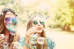 Двойные сестры делая пузыри мыла в парке Стоковое Изображение RF