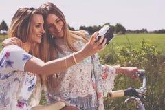 Двойные сестры делая selfie с ретро камерой Стоковое фото RF