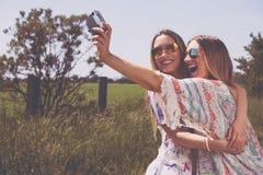 Двойные сестры делая selfie с ретро камерой Стоковое Фото