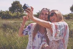Двойные сестры делая selfie с ретро камерой Стоковые Изображения