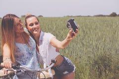 Двойные сестры делая selfie с ретро камерой Стоковая Фотография