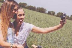 Двойные сестры делая selfie с ретро камерой Стоковые Фотографии RF