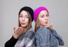 Двойные сестры одетые в теплых одеждах зимы Стоковая Фотография