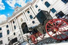 Дворец Hofburg с традиционным экипажом Fiaker в вене, Австрии Стоковая Фотография