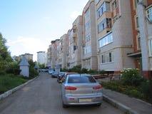 Двор дороги, автомобилей, цветков и домов в городе Стоковое Изображение RF