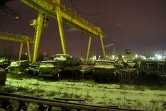 Двор старья русских военного транспортного средства и танков Отремонтируйте фабрику, кран на ноче Стоковые Изображения RF