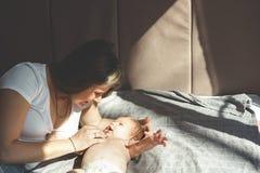 Двухмесячный младенец без одежд, нагой, лежа в пеленке и усмехаясь на матери стоковая фотография rf