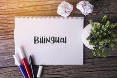 Двуязычное слово с блокнотом и зеленым растением на деревянной предпосылке Стоковое Фото