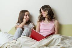 2 девочка-подростка в их пижамах сидят в кровати дома и смотрят книгу Стоковые Изображения RF
