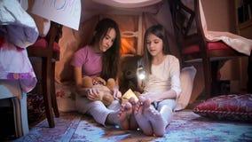 2 девочка-подростка в пижамах сидя на поле на книге спальни и чтения на ноче Стоковая Фотография