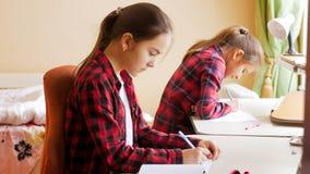 2 девочка-подростка делая домашнюю работу в спальне за столом Стоковые Изображения RF