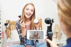 2 девочка-подростка записывая блог красоты в спальне Стоковое Изображение RF