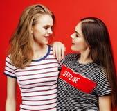 2 девочка-подростка лучших другов совместно имея потеху, представлять эмоциональный на красной предпосылке, усмехаться besties сч Стоковые Изображения