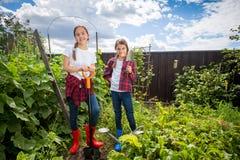 2 девочка-подростка представляя в саде с садовничая инструментами Стоковые Изображения RF