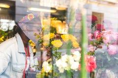 Девочка-подростки Афро американские пахнуть желтыми розовыми цветками стоковое изображение