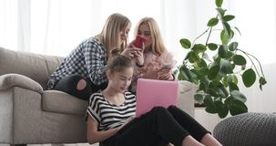 Девочка-подростки занятые просматривающ социальные средства массовой информации на мобильном телефоне и ноутбуке сток-видео