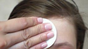 Девочка-подростки прикладывают moisturizing сливк стороны для угорь Девушка трет ее лоб с салфеткой Косметические процедуры для стоковые фото