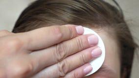 Девочка-подростки прикладывают moisturizing сливк стороны для угорь Девушка трет ее лоб с салфеткой Косметические процедуры для стоковое фото