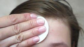 Девочка-подростки прикладывают moisturizing сливк стороны для угорь Девушка трет ее лоб с салфеткой Косметические процедуры для стоковые фотографии rf