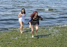 Девочка-подросток бежать от воды на шламе предусматривал пляж Alki пока ее вахты кузена с занятностью стоковые изображения