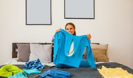 Девочка-подросток выбирая одежды на кровати в комнате стоковое изображение