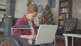 Девочка-подросток вывел из строя в кресло-коляске, сидя на ноутбуке, против рождественской елки акции видеоматериалы