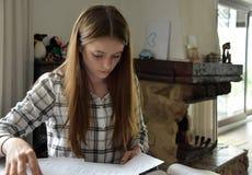 Девочка-подросток делая ее домашнюю работу математик стоковые фотографии rf