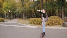 Девочка-подросток едет электронный самокат девушка танцует на волчке сток-видео