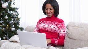 Девочка-подросток используя ноутбук на софе рядом с рождественской елкой дома сток-видео