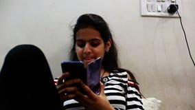 Девочка-подросток используя сидеть в ее комнате и использование смартфона акции видеоматериалы