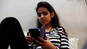 Девочка-подросток используя сидеть в ее комнате и использование смартфона сток-видео