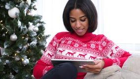 Девочка-подросток используя цифровой планшет во время рождества видеоматериал