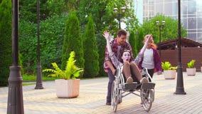 Девочка-подросток и человек который носит неработающую женщину в кресло-коляске в парке видеоматериал