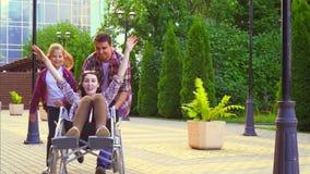 Девочка-подросток и человек который носит неработающую женщину в кресло-коляске в парке Медленный mo акции видеоматериалы