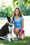 Девочка-подросток и черная собака стоковые изображения