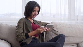 Девочка-подросток наслаждаясь содержанием на цифровом планшете сток-видео